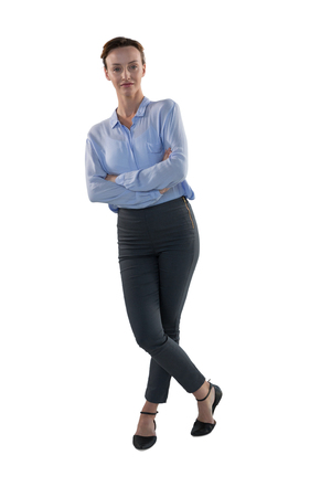 Female executive standing with arms crossed against white background