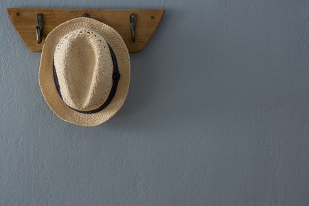 Straw hat hanging on hook against wall 免版税图像