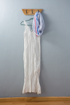 White dress and scarf hanging on hook against wall