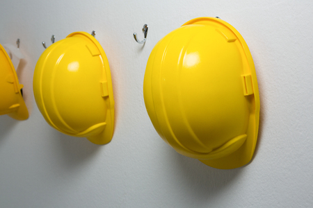 Close-up of hard hats hanging on hook