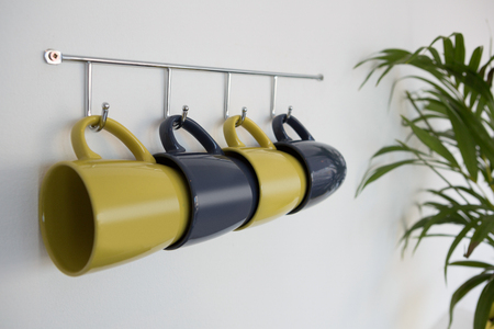 hook up: Close-up of colorful mugs hanging on hook against white wall