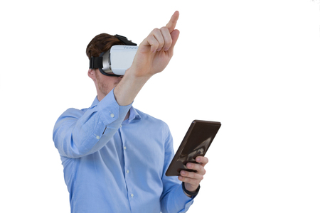 Male executive using virtual reality headset and digital tablet against white background