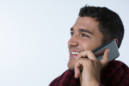 Close-up of smiling man talking on mobile phone against white background