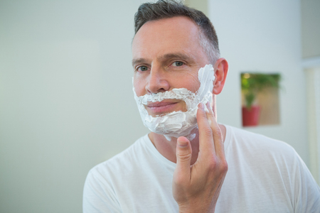 Man applying shaving foam on his face in bathroom