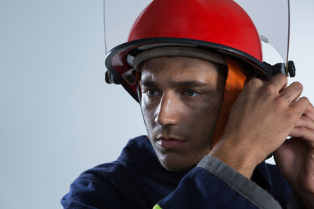 Close-up of fireman adjusting his safety helmet against white background