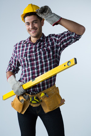 Portrait of male architect holding measuring equipment against white background Lizenzfreie Bilder
