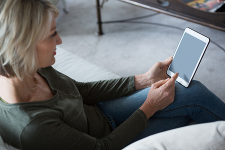 Beautiful woman using digital tablet in living room at home