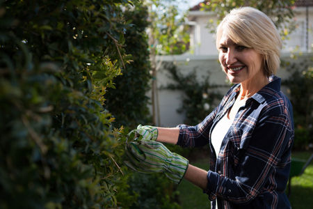 Portrait of happy woman pruning plants in garden