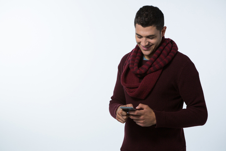 Smiling man in winter cloth using mobile phone against white background Imagens