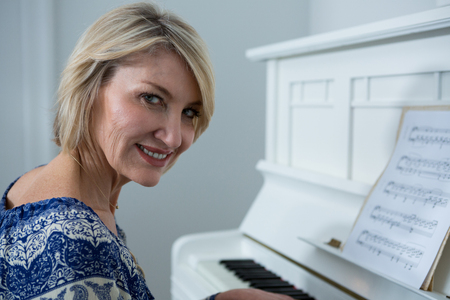 Portrait beautiful woman playing piano at home