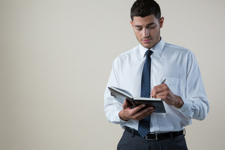 Confident executive writing on diary against white background