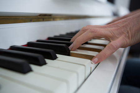 Close-up of woman playing piano at home