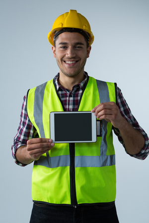 Smiling male architect showing digital tablet against white background Lizenzfreie Bilder