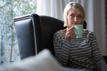 Thoughtful woman having coffee in living room at home
