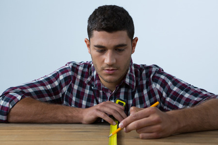 Male architect measuring wooden plank with tape measure against white background