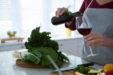 キッチンのテーブルに赤ワインを持つ女性の中間セクション