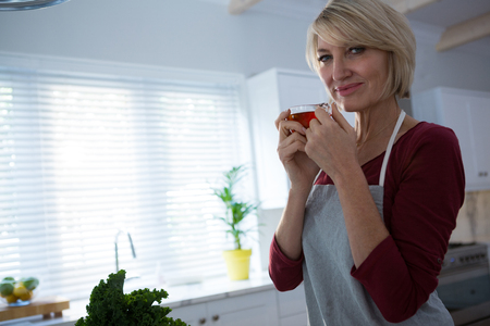Portrait of happy woman having lemon tea in kitchen