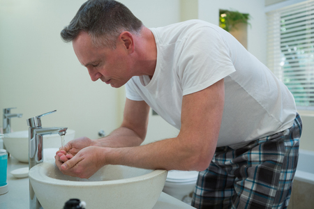 Man spraying water on his face after shaving in the bathroom at home Lizenzfreie Bilder
