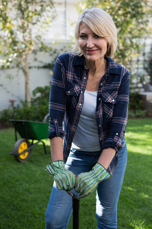 Portrait of beautiful woman standing with gardening equipment