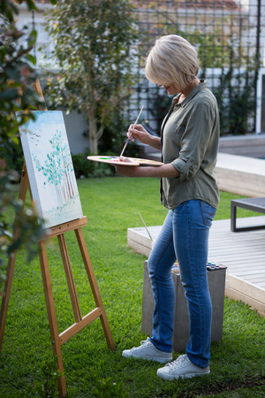 Woman painting on canvas in lawn