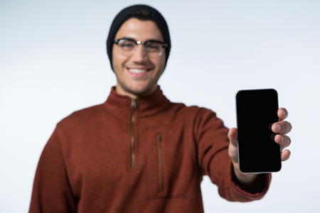 Smiling man in winter cloth holding mobile phone against white background
