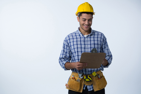 Happy male architect looking at clipboard against white background