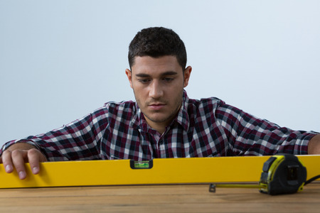 Male architect measuring plywood with engineer scale against white background