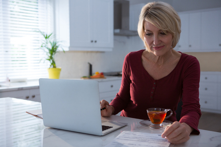 Woman looking at bill in kitchen at home Lizenzfreie Bilder