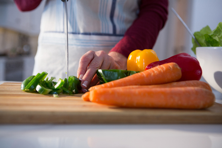 Mid section of woman chopping vegetables in kitchen