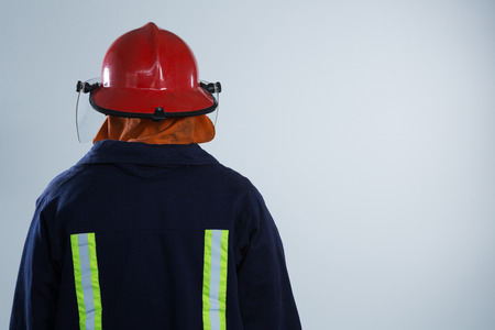 Rear view of fiireman standing against white background  Stock Photo