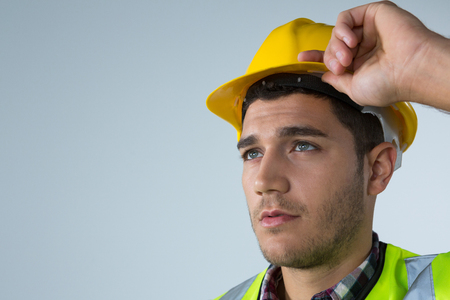 Thoughtful architect holding hard hat against white background