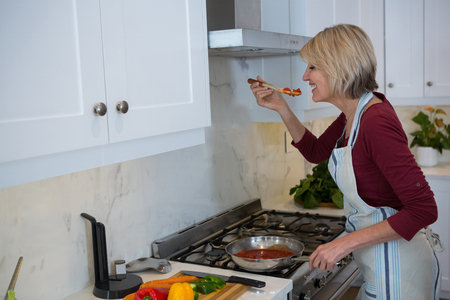 Beautiful woman tasting food while cooking in kitchen Lizenzfreie Bilder
