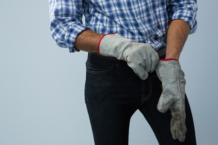Mid section of male architect wearing gloves against white background