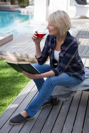 Beautiful woman reading book while drinking wine in porch on a sunny day