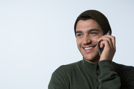 Man in winter cloth talking on mobile phone against white background