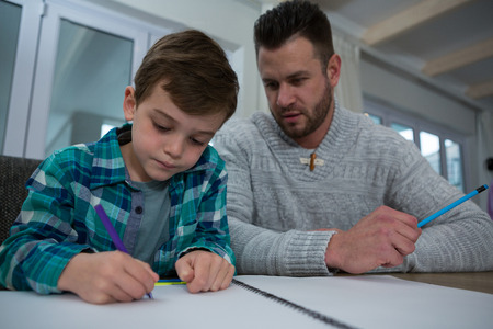 Father assisting son in his studies at table Lizenzfreie Bilder