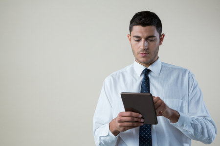 Confident businessman using digital tablet against white background Lizenzfreie Bilder