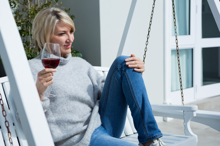 Thoughtful woman having wine in porch on a sunny day
