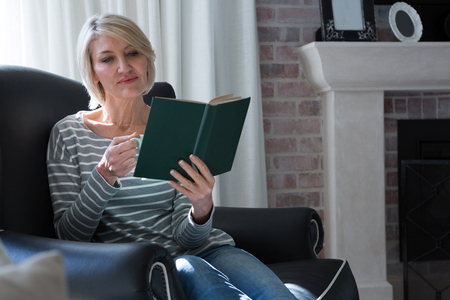 Beautiful woman reading book while having coffee in living room