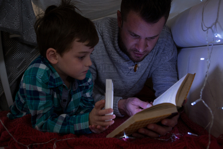 Father and son reading book under shelter in bedroom