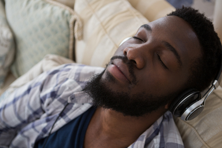 Man sleeping while listening to music at home