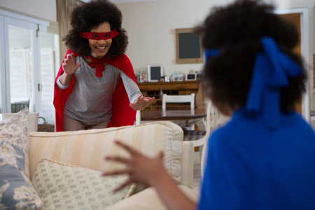 Mother and daughter pretending to be superhero at home