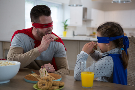 Father and daughter pretending to be superhero while having breakfast