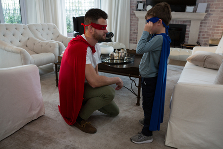 Father and son pretending to be superhero at home
