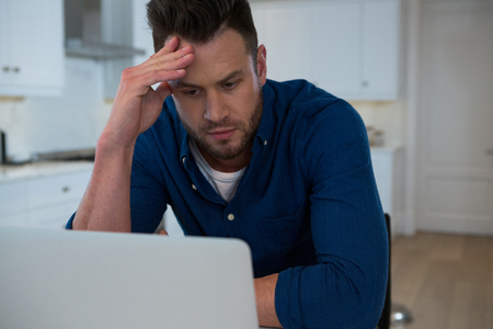 Tensed man using laptop in kitchen at home Lizenzfreie Bilder