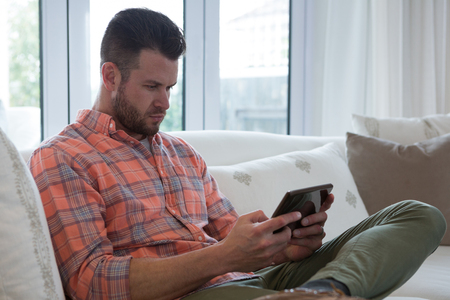 Man using digital tablet in living room at home Lizenzfreie Bilder