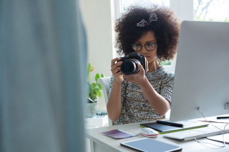 Graphic designer taking picture with digital camera at desk