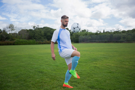 Football player juggling soccer ball in the ground Stock Photo