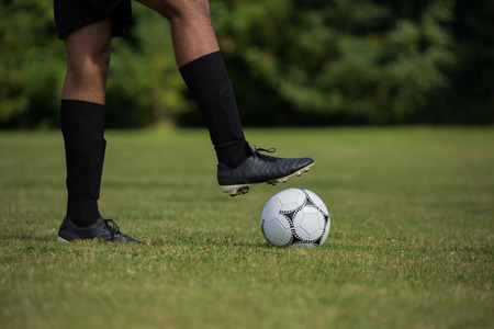 Football player ready to kick the soccer ball in the ground