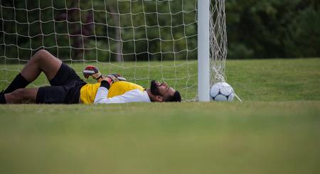 Goalkeeper relaxing near goalpost in football stadium Banco de Imagens - 89774309